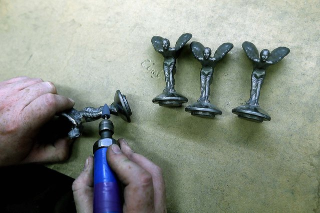 Worker Barry Smith finishes some of the iconic mascots. (Photo by Stefan Wermuth/Reuters)