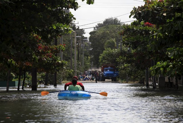 People in a boat try to make their way through a flooded street in Havana January 23, 2016. (Photo by Enrique de la Osa/Reuters)