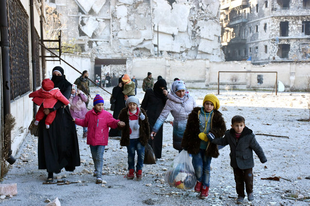 A handout photograph released by the official Syrian Arab News Agency (SANA) shows people carrying their belonging and leaving the eastern neighborhoods of Aleppo, Syria, 07 December 2016. According to SANA, Syrian army secured the exit of new batches of civilians who were besieged by 'terrorists' in east of Aleppo after recapturing several neighborhoods. According to Syrian official and foreign NGO sources, the Syrian government forces recovered more East Aleppo districts, where they are involved in a large-scale offensive to expel the insurgents. Syrian rebel factions have also fully retreated from the historic center of Aleppo. (Photo by EPA/SANA)