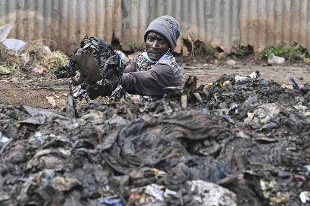 A Kenyan environment activist unclogs drainage ahead of World Environmental Day celebrations in Riruta, Nairobi, on June 4, 2021. World Environment Day is the United Nations day for encouraging worldwide awareness and action to protect our environment. (Photo by Simon Maina/AFP Photo)