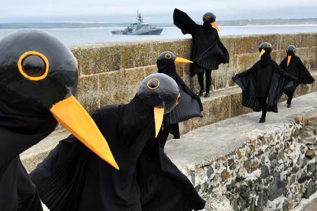 Climate change activists dressed up as black birds protest in St. Ives, on the sidelines of the G7 summit in Cornwall, Britain, June 11, 2021. (Photo by Dylan Martinez/Reuters)