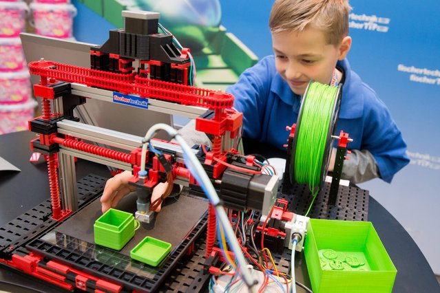 """Quirin operating the """"fischertechnik 3-D-Printer"""", a 3D printer from a modular cosnstruction system by manufacturer fischertechnik, during the new products show at the 67th international toys trade fair (Spielwarenmesse) in Nuremberg, Germany, 26 January 2016. The world's largest toys trade fair runs from 27 January to 01 February 2016. (Photo by Daniel Karmann/EPA)"""