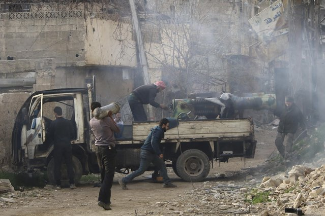 Rebel fighters from the Free Syrian Army's Al Rahman legion prepare to fire a locally-made weapon towards forces loyal to Syria's President Bashar al-Assad on the frontline, in the eastern Damascus suburb of Ghouta March 12, 2015. (Photo by Diaa Al-Din/Reuters)