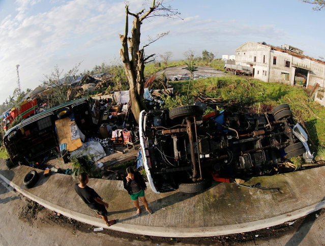 Filipino typhoon victims stand next to toppled trucks in the town of Pili, Camarines Sur province, Philippines, 27 December 2016. At least six people were killed and eight remain missing in the Philippines following the passage of Typhoon Nock-Ten, which left a trail of destruction in the central part of the archipelago, according to local media. Authorities in the eastern provinces of Albay and Catanduanes have declared a state of emergency, a measure that allows immediate disbursements of money to deal with the catastrophe. The National Disaster Risk Reduction and Management Council, which coordinates the response and issues periodic bulletins on the situation, has reported that 383,087 people have been evacuated and directly 72,869 affected. Nock-Ten is the third typhoon in the country's recent history that struck during the Christmas holiday season, after Lee in 1981 and Jean in 1947, both Category 2 storms. (Photo by Francis R. Malasig/EPA)