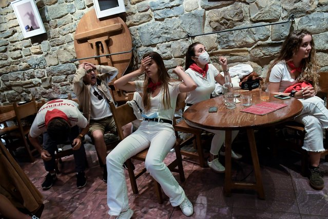 Spain's fans react after their team lost the match against Italy while watching the match in a bar during the Euro 2020 soccer championship semifinal match between Italy and Spain, in Pamplona, northern Spain, Tuesday, July 6, 2021. (Photo by Alvaro Barrientos/AP Photo)