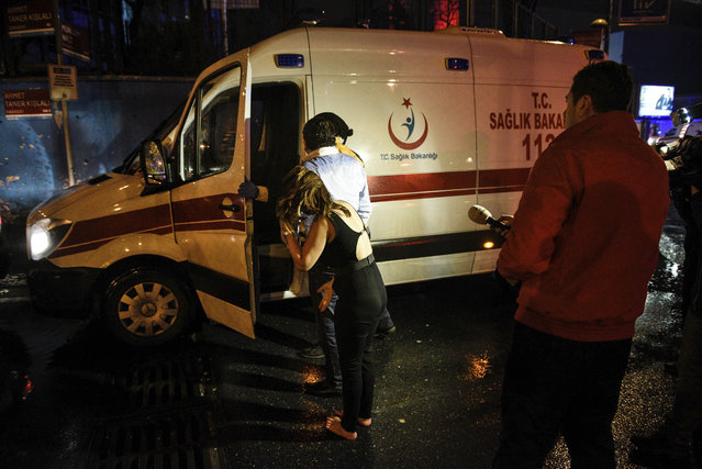 People talk to medics in an ambulance near the scene of an attack in Istanbul, early Sunday, January 1, 2017. Turkey's state-run news agency said an armed assailant has opened fire at a nightclub in Istanbul during New Year's celebrations. (Photo by AP Photo)