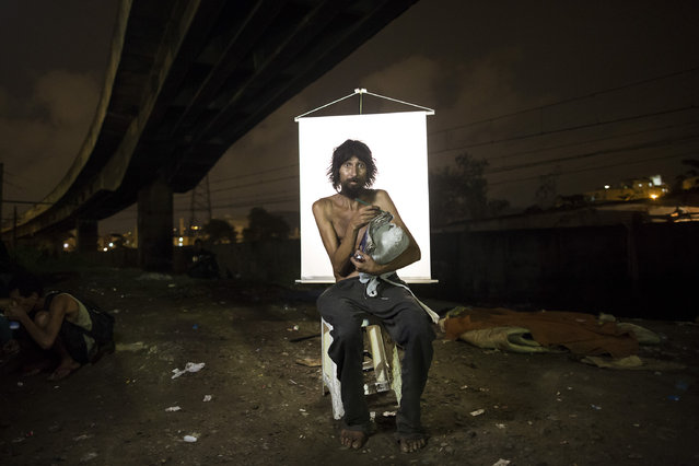 "In this March 17, 2015 photo, Renato Dias, 39, writes in his notebook as he poses for a portrait in an open-air crack cocaine market, known as a ""cracolandia"" or crackland, where users can buy crack, and smoke it in plain sight, day or night, in Rio de Janeiro, Brazil. Dias, who has been using crack for about 4 years, says he uses his notebook as a form of distraction. He writes about super heroes and dreams of becoming one. (Photo by Felipe Dana/AP Photo)"