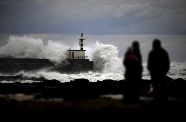 People look at huge waves crashing on the San Esteban de Pravia seafront, northern Spanish region of Asturias February 8, 2016. (Photo by Eloy Alonso/Reuters)
