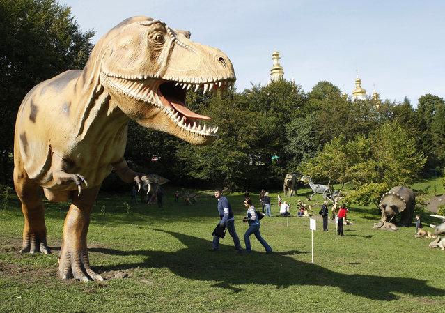 People visit the World of Dinosaurs exhibition at Pechersk Landscape Park in Kiev, Ukraine, September 10, 2010. (Photo by Gleb Garanich/Reuters)