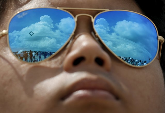Pilot Akmal Bin Abdul Kahar watches South Korea's Black Eagles aerobatics team perform a manoeuvre during an aerial display at the Singapore Airshow at Changi Exhibition Center February 18, 2016. (Photo by Edgar Su/Reuters)