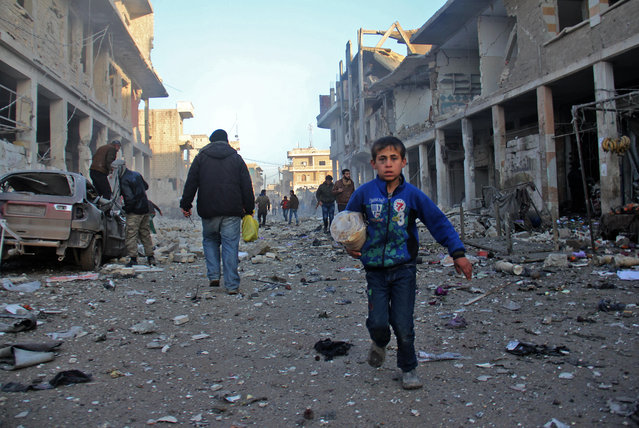 A Syrian boy runs while carrying bread following a reported airstrike by government forces, in the Syrian town of Binnish, on the outskirts of Idlib, on January 12, 2017. At least 22 jihadists were killed in air strikes on Idlib province over the past 24 hours, the Syrian Observatory for Human Rights said. (Photo by Omar Haj Kadour/AFP Photo)