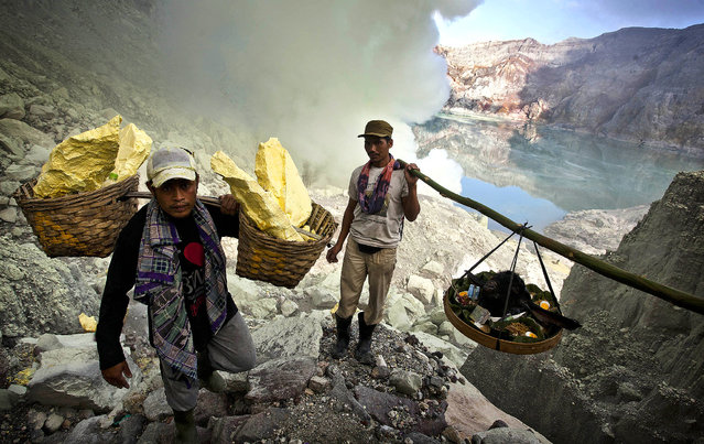 Miners carry a goats head for burial in the crater as part of an annual offering ceremony on the Ijen volcano on December 17, 2013 in Yogyakarta, Indonesia. (Photo by Ulet Ifansasti/Getty Images)