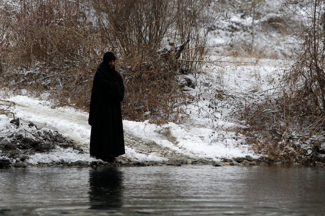 A woman stands on a river bank during the Epiphany day celebration in Bitushe, Macedonia January 19, 2017. (Photo by Ognen Teofilovski/Reuters)