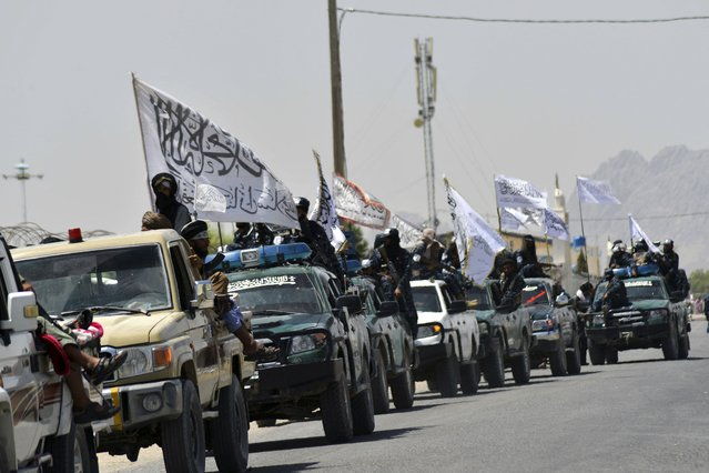 Taliban fighters atop vehicles with Taliban flags parade along a road to celebrate after the US pulled all its troops out of Afghanistan, in Kandahar on September 1, 2021 following the Taliban's military takeover of the country. (Photo by Javed Tanveer/AFP Photo)