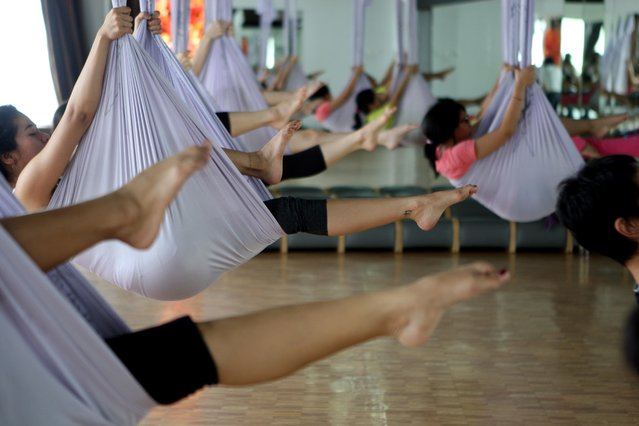 Some women doing yoga on the hammocks as they attend the Anti-Gravity yoga class at Svarga e-Motion Sanctuary at Dharmawangsa Square, Jakarta, Saturday, April 18, 2015. (Photo by Jurnasyanto Sukarno/JG Photo)