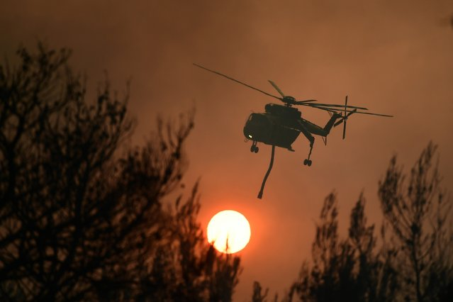 An helicopter operates during a wildfire in Kryoneri area, northern Athens, Greece, Thursday, August 5, 2021. Wildfires rekindled outside Athens and forced more evacuations around southern Greece Thursday as weather conditions worsened and firefighters in a round-the-clock battle stopped the flames just outside the birthplace of the ancient Olympics. (Photo by Michael Varaklas/AP Photo)