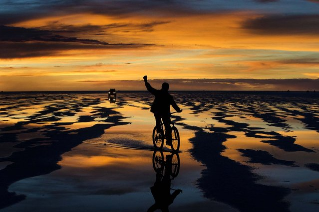 A bicycle rider waves to friends at the Uyuni Salt Flats, on January 11, 2014. (Photo by Victor R. Caivano/Associated Press)
