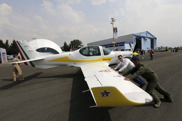 A pilot (R) and other people move a G 120TP aircraft, after the inauguration of the first Aerospace Fair 2015 at the Santa Lucsia military airbase in Tecamac near Mexico City April 22, 2015. Mexico's biggest gathering in aerospace technology kicked off on Wednesday with a demonstration of state-of-the-art aircraft from Mexico and abroad as the Latin American country emerges as a promising young player in the aviation industry. (Photo by Henry Romero/Reuters)