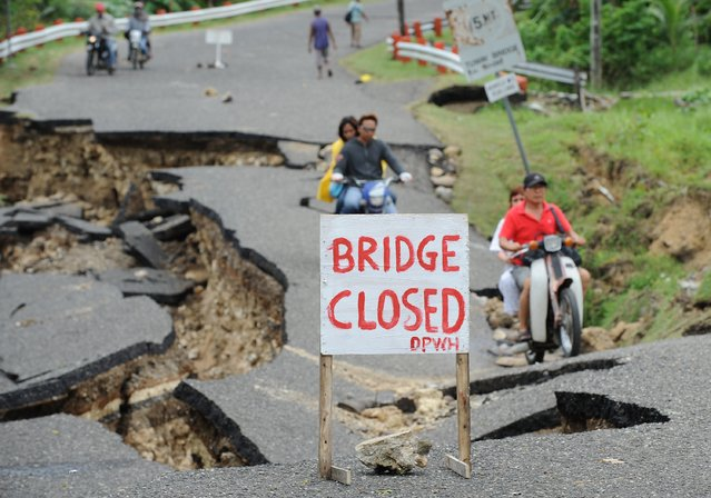 Motorists cross a damaged road destroyed at the height of the powerful earthquake in Guihulngan town, Negros Oriental province, central Philippines on February 9, 2012. (Photo by Ted Aljibe/AFP Photo)