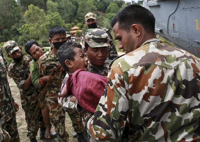 An injured boy cries in pain as he is carried by Nepal Army personnel to a helicopter following Saturday's earthquake in Sindhupalchowk, Nepal, April 28, 2015. (Photo by Danish Siddiqui/Reuters)