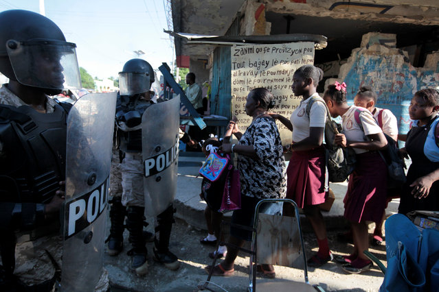A woman and several schoolgirls pass a police line blocking a street to control a demonstration organised to protest against the results of the presidential elections, in the streets of Port-au-Prince, Haiti, December 5, 2016. (Photo by Andres Martinez Casares/Reuters)