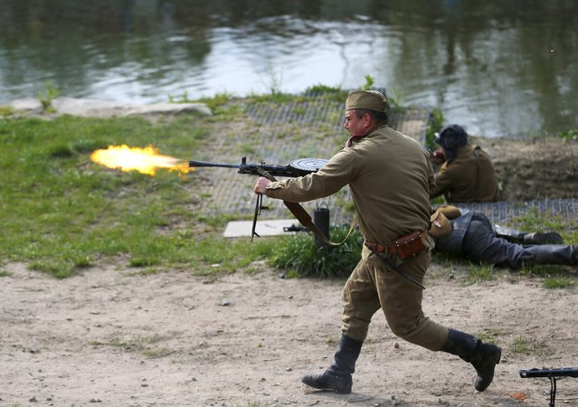 A man dressed in a World War II Red Army uniform fires during a re-enactment battle between the Soviet Red Army and German troops during the 70th anniversary of the liberation of Ostrava, in Ostrava, Czech Republic, April 30, 2015. (Photo by Laszlo Balogh/Reuters)
