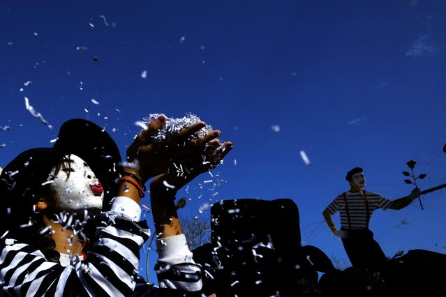 A child blowing confetti from her hands during a Carnival parade in Cyprus' coastal city of Limassol, Sunday, March 13, 2016. Limassol's long-established parade is Cyprus' biggest and most famous, drawing revelers from across the east Mediterranean island. This year's parade drew huge crowds as people sought lighthearted reprieve from the bailed-out country's recession. The parade marks the start of the 40-day fasting period of Lent in the run-up to the Orthodox Christian Easter. (Photo by Petros Karadjias/AP Photo)