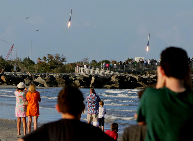 Spectators watch from Jetty Park as booster rocket engines approach landing pads, after a SpaceX Falcon Heavy rocket, carrying the Arabsat 6A communications satellite, lifted off from the Kennedy Space Center in Cape Canaveral , Florida, U.S., April 11, 2019. (Photo by Joe Rimkus Jr./Reuters)