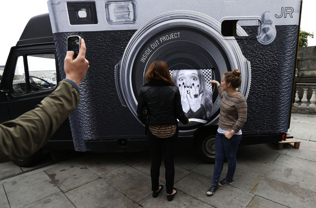 "A woman looks on as her photograph is printed for the ""Actions"" project on the Terrace at Somerset House in London October 7, 2013. (Photo by Suzanne Plunkett/Reuters)"