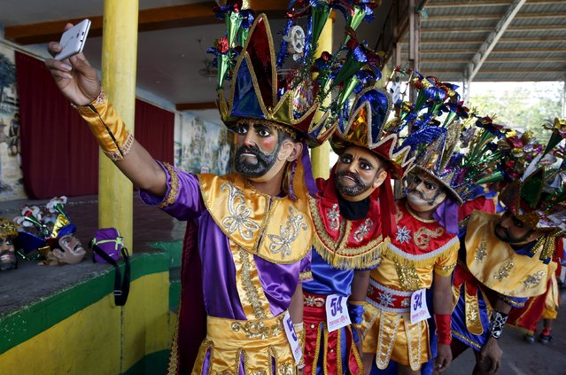 """Penitents wearing masks, known locally as """"Morions"""" take a selfie during the start of Holy Week celebrations in Mogpog, Marinduque in central Philippines March 21, 2016. (Photo by Erik De Castro/Reuters)"""