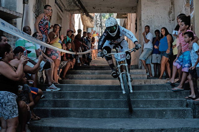 A competitor goes down steps of an alley during the Favelas Mountain Bike circuit at Turano shantytown in Rio de Janeiro, Brazil, on May 3, 2015. The Favelas Mountain Bike circuit started on March its second edition after 2013, and will be competed in eight stages until November for both Downhill and Cross-country categories through six different pacified favelas. (Photo by Yasuyoshi Chiba/AFP Photo)