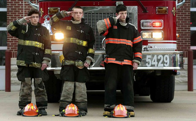 Swansea Fire Department cadets Drake Parnell, Aiden Ross and Braden Schnarre, all 14 years old, salute the casket carrying the body of firefighter Brett Korves on Huntwood Road as a procession passes the fire station, Friday, April 5, 2019 in St. Louis. Korves, a ten year firefighter, was killed in an off-duty car accident on Thursday in north St. Louis County. (Photo by Robert Cohen/St. Louis Post-Dispatch via AP Photo)