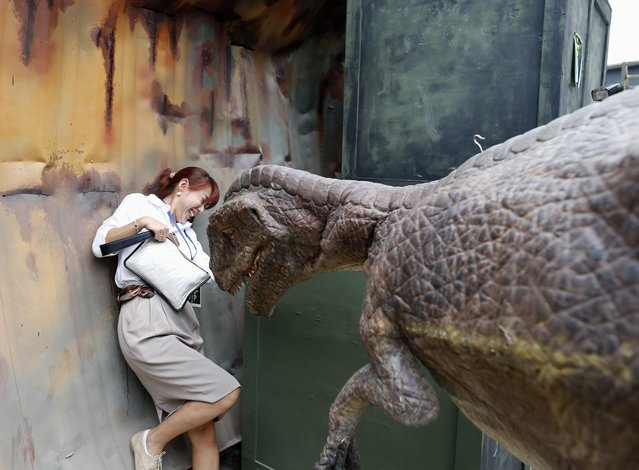 A Thai visitor appears to be frightened by a life-size Velociraptor model also known as Raptor at the Dinosaur Planet theme park in Bangkok, Thailand, 25 March 2016. The 500 million baht (14 million US dollars or 12 million euro) theme park opening in the Thai capital aimed to attract more than 15,000 visitors a day featuring a chance to experience more than 200 dinosaurs from various species that are brought back to life. (Photo by Rungroj Yongrit/EPA)