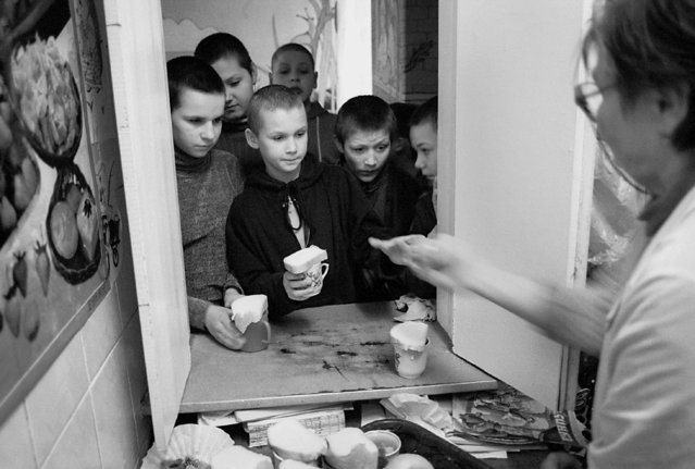 Children at the Maikovska state centre in Kiev receive their meagre dinner consisting of a cup of soup and a piece of bread, 2002. (Photo by Kurt Vinion /Getty Images)