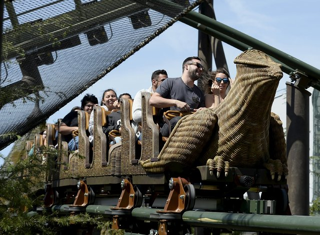 """Guests take a ride on a rollercoaster outside the Hogwarts School during a soft opening and media tour of """"The Wizarding World of Harry Potter"""" theme park at the Universal Studios Hollywood in Los Angeles, California in this picture taken March 22, 2016. (Photo by Kevork Djansezian/Reuters)"""