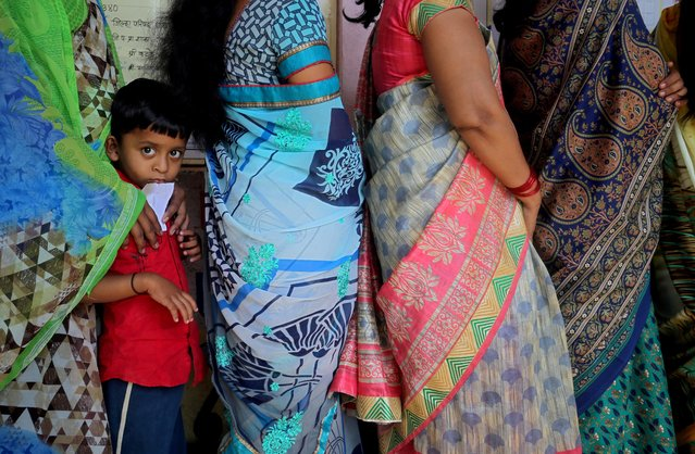 A boy looks on as he stands in a queue with women waiting to cast their votes at a polling station during the third phase of the general election on the outskirts of Pune, April 23, 2019. (Photo by Francis Mascarenhas/Reuters)