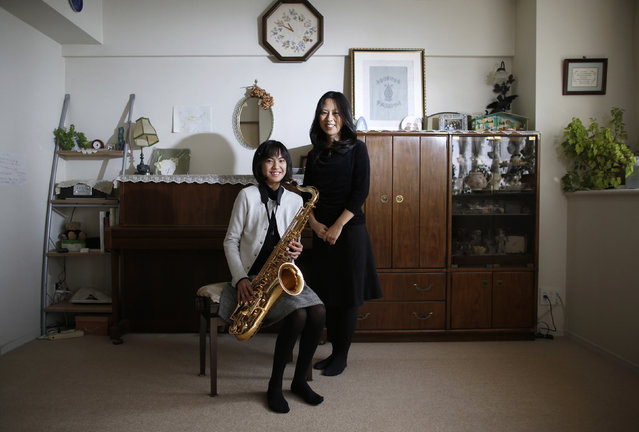 Manami Miyazaki (R), 39, and her daughter Nanaha, 13 and holding her alto saxophone, pose for a photograph at their home in Tokyo February 3, 2014. Manami, who is a housewife, studied until she was 20. Her ambition was to work somewhere where she could meet lots of people. She hopes that her daughter will build a loving home with a happy marriage. (Photo by Toru Hanai/Reuters)