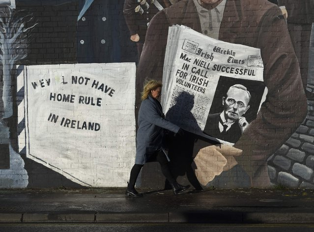 A woman walks past a mural on the Falls Road a day after Northern Ireland's Deputy First Minister Martin McGuinness resigned, throwing the devolved joint administration into crisis, in Belfast Northern Ireland, January 10, 2017. (Photo by Clodagh Kilcoyne/Reuters)