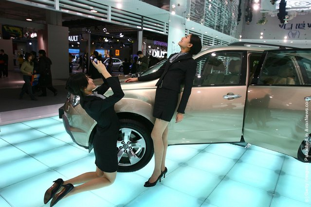 A model poses for a photo at an exhibition stand of the 2006 International Automotive Exhibition