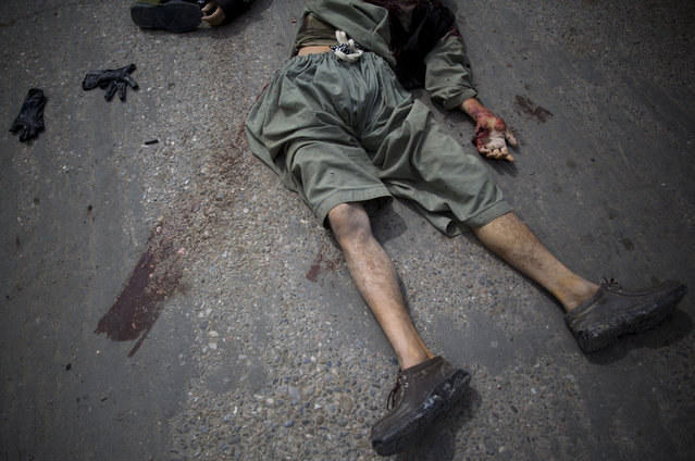 A dead suicide bomber lies on the street in the center of Kandahar, Afghanistan, Wednesday, March 12, 2014, after an attack on the former Afghan intelligence headquarters. Police officials said three insurgents who tried to storm the former headquarters of Afghanistan's intelligence service in southern Kandahar died in a gunbattle with security forces. (Photo by Anja Niedringhaus/AP Photo)