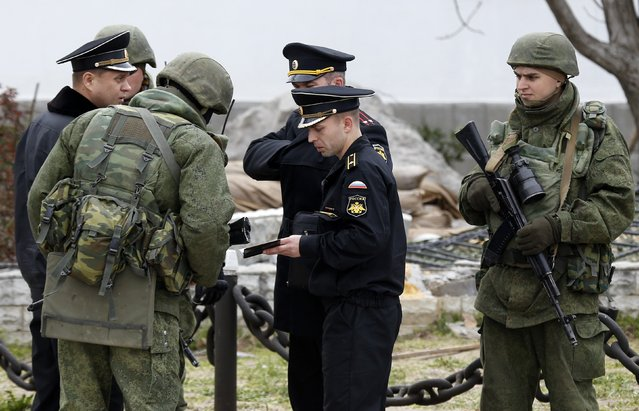 Armed men, believed to be Russian servicemen, check documents of Russian navy officers who enter the territory of the naval headquarters in Sevastopol, March 19, 2014. Around a dozen Ukrainian servicemen, unarmed and in civilian clothes, walked out of the Ukrainian naval headquarters in the Crimean port of Sevastopol on Wednesday after it was taken over by pro-Russian forces, a Reuters witness said. (Photo by Vasily Fedosenko/Reuters)