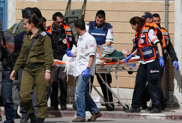 Israeli medics tend to a wounded Palestinian woman, who according to Israeli police was shot after she was suspected by security guards and ignored calls to stop, at Qalandiya checkpoint near the West Bank city of Ramallah February 27, 2017. (Photo by Ammar Awad/Reuters)