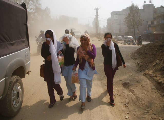 Pedestrians cover their face as they walk along the dusty road in Kathmandu, Nepal February 27, 2017. Nepal has forced 2,500 old vehicles off roads in its capital city of Kathmandu, part of a fight against alarming air pollution levels that have hit nine times World Health Organisation (WHO) limits. Air pollution has been a chronic problem in rapidly growing Kathmandu, which sits in a Himalayan valley and is home to more than 3mn people. Rising public anger with the smog is turning into a headache for a beleaguered government headed by former Maoist rebels. Dust from road works, exhaust from old, poorly maintained vehicles and smoke from coal-burning brick kilns blend in a murky haze that hangs over the ancient city, raising the risk of cancer, stroke, asthma and high blood pressure, experts say. Officials hope the ban on vehicles more than 20 years old will be a step towards a cleaner future. (Photo by Navesh Chitrakar/Reuters)