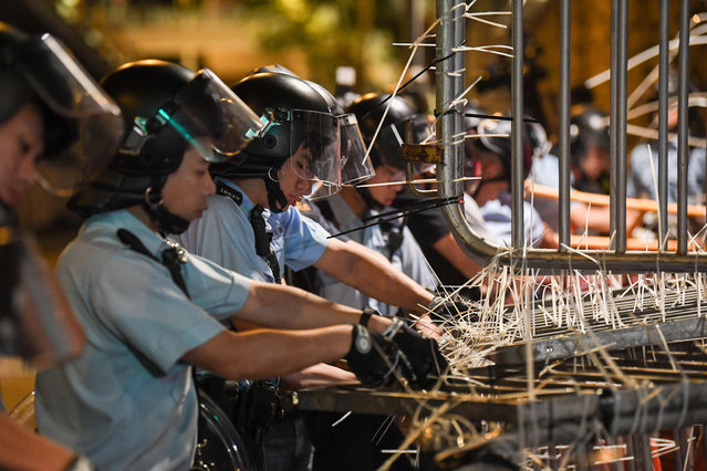 Police clear barricades which were set up by protesters outside the police headquarters in Hong Kong early on June 22, 2019. Hong Kong police on June 22 vowed to pursue the ringleaders of a 15-hour blockade of their headquarters which involved thousands of anti-government demonstrators as a push to oust the city's pro-Beijing leader evolves. (Photo by Anthony Wallace/AFP Photo)