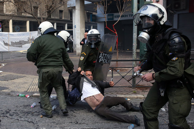 Greek policemen arrest a farmer during a protest of farmers from Crete island, outside of the Agriculture Ministry, in Athens, Greece, 08 March 2017. Farmers protested against the government's tax and pension system reforms. (Photo by Orestis Panagiotou/EPA)