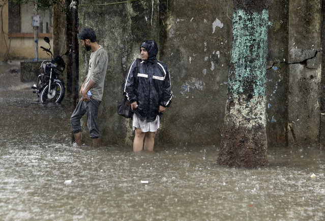 People wade through a waterlogged street following heavy rains in Mumbai, India, Tuesday, July 2, 2019. Heavy monsoon rains in western India caused at least three walls to collapse onto huts and city shanties, killing more than two dozen people and injuring dozens of others, officials said Tuesday, as forecasters warned of more rains. (Photo by Rajanish Kakade/AP Photo)