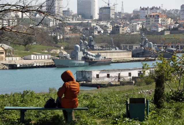 A local woman sits on a bench atop a hill overlooking Russian Navy vessels anchored at a navy base in the Ukrainian Black Sea port of Sevastopol in Crimea, March 30, 2014. (Photo by Yannis Behrakis/Reuters)