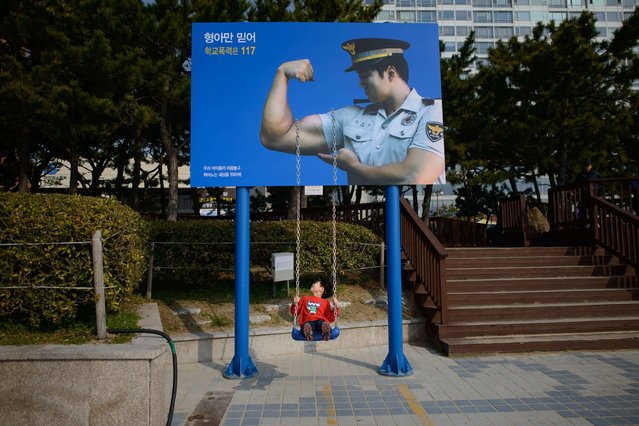 In a photo taken March 16, 2014, a child plays on a swing beneath a poster of a policeman in Busan. South Korea's central bank kept its key interest rate unchanged at 2.5 percent on March 13 for the 10th consecutive month, citing mixed signs of a global recovery. (Photo by Ed Jones/AFP Photo)