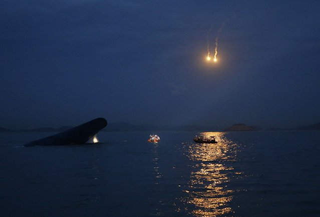 """South Korean ferry """"Sewol"""" (L) is seen sinking at the sea off Jindo, as lighting flares are released for a night search, April 16, 2014. (Photo by Kim Hong-Ji/Reuters)"""