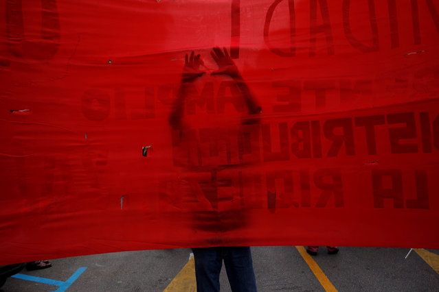 A supporter of the Communist party uses a scissors to make holes on a banner as he takes part in a May Day rally in Malaga, Spain, May 1, 2016. (Photo by Jon Nazca/Reuters)
